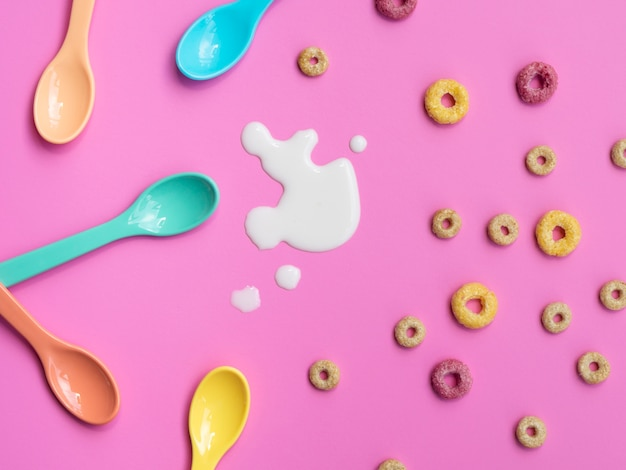 Coloured fruity loops and spoons on pink background