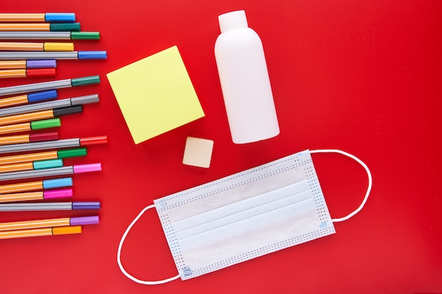 Coloured markers and mask on a red background. back to school concept and protection against coving.