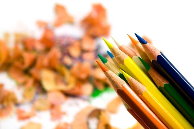 Coloured pensils over sawdust background