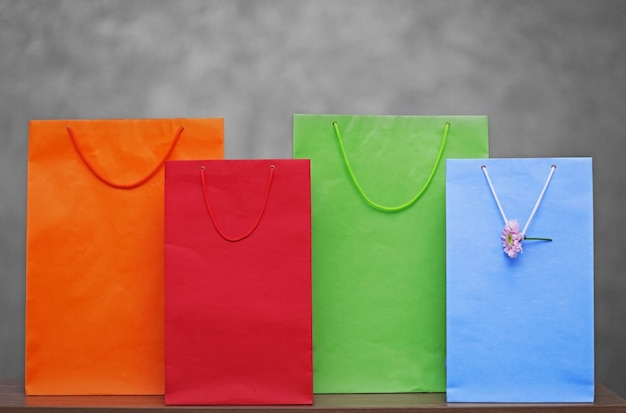 灰色の表面に色付きのショッピングバッグ