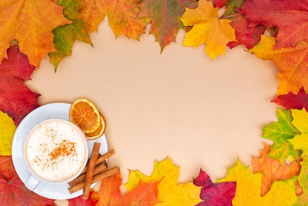 カラフルな秋のカエデは、スパイスの効いたコーヒーのカップでフレームを残します。シナモンとカプチーノ。