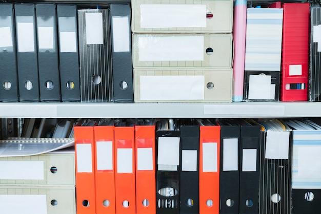 선반에 파일이 있는 다채로운 빈 블라인드 폴더. 보관, 사무실이나 도서관에 있는 문서 더미. 물리적 문서 저장 장치