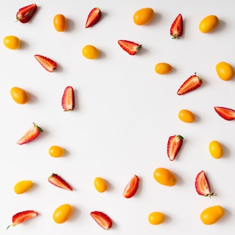 Colourful bright pattern made of kumquat fruit and strawberries. flat lay.