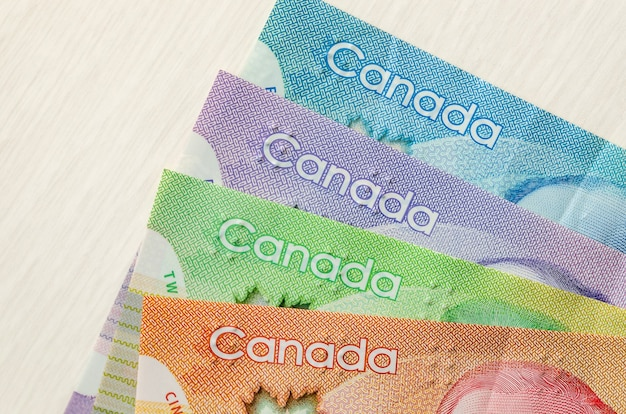 Colourful canadian dollar banknotes on wooden surface