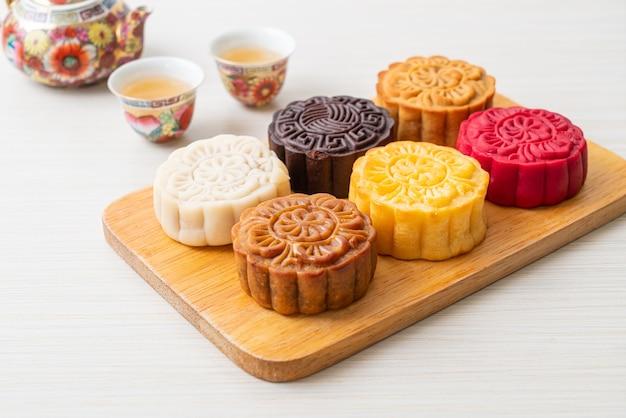Красочный китайский лунный пирог со смешанным вкусом на деревянной тарелке