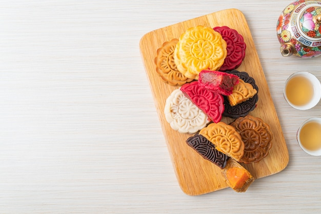 Colourful chinese moon cake with mixed flavour on wood plate