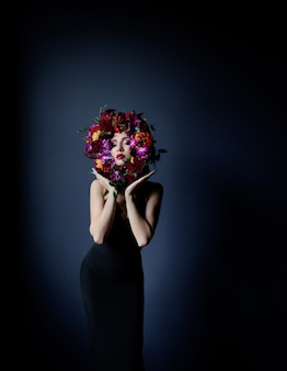 Colourful circle made of fresh flowers on the beautiful girl's face, woman dressed in black tight dress on the dark blue background