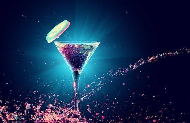 Красочный коктейль в стакане с вкраплениями на темном фоне