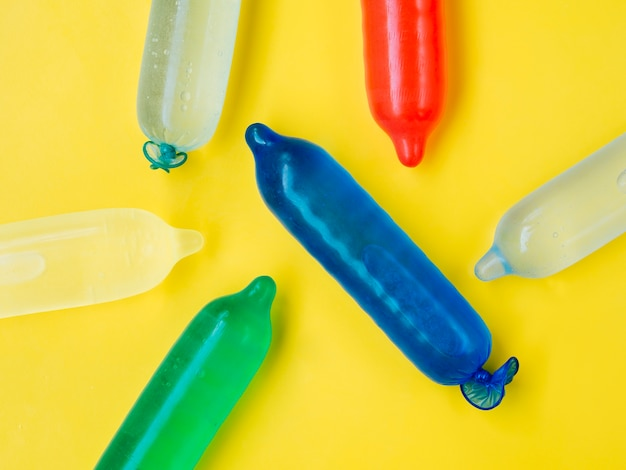 Colourful condoms filled with water on yellow background