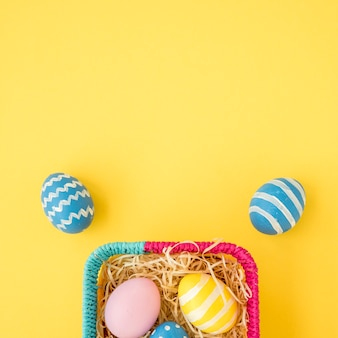 Colourful easter eggs in  basket on yellow table