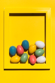 Colourful easter eggs in big frame on table