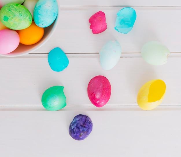 Colourful easter eggs in bowl near shell on desk