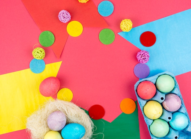 Colourful easter eggs in box and in nest on table