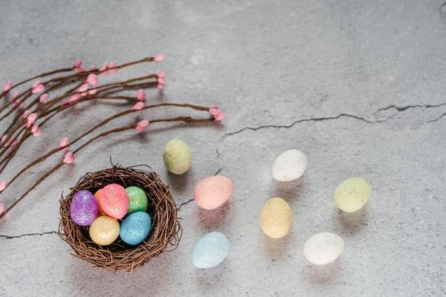 灰色のセメントの背景に装飾的な柳の枝、お祝いのイースターの装飾と鳥の巣のカラフルなイースターエッグ