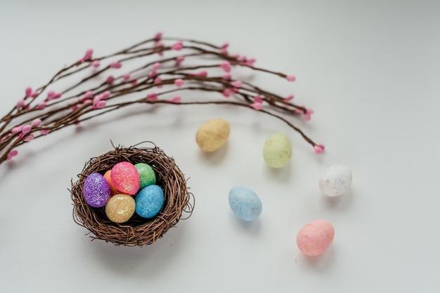 Красочные пасхальные яйца в птичьем гнезде с пасхальными декоративными ветками