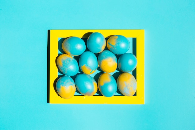 테이블에 노란색 프레임에 다채로운 부활절 달걀