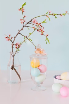 Colourful easter eggs near flower twig in vase with water and bowl