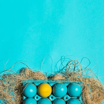 Colourful easter eggs in rack on hay on blue table