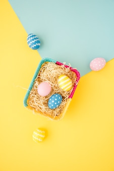 Colourful easter eggs in small basket on table