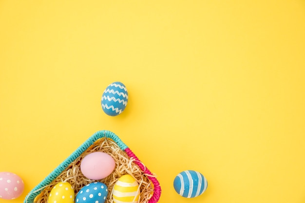 Colourful easter eggs in small basket on yellow table
