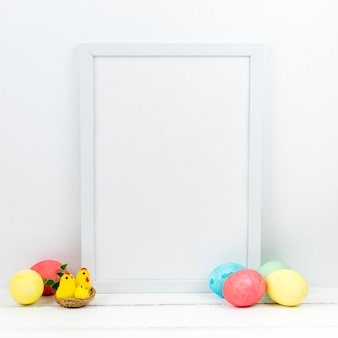 Colourful easter eggs with blank frame on table