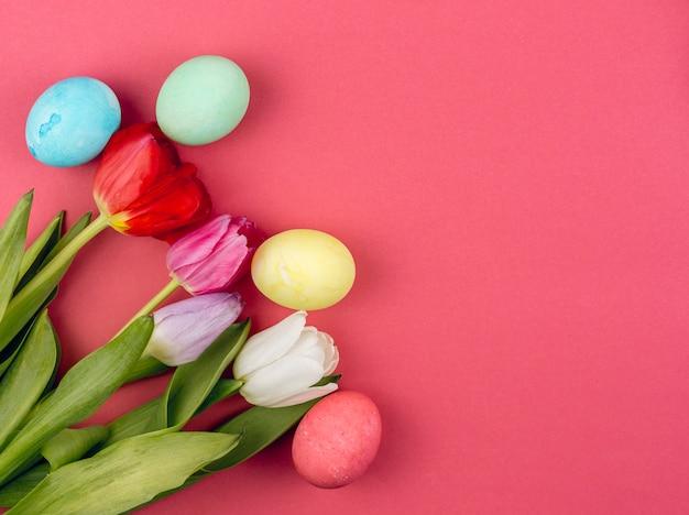 빨간 테이블에 튤립과 다채로운 부활절 달걀