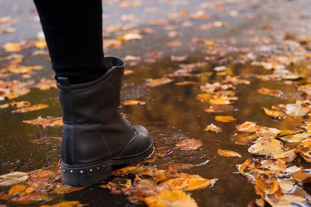 池の湖の水に色とりどりの紅葉が咲き、水たまりを通り抜ける通行人のブーツ。雨の秋の天気