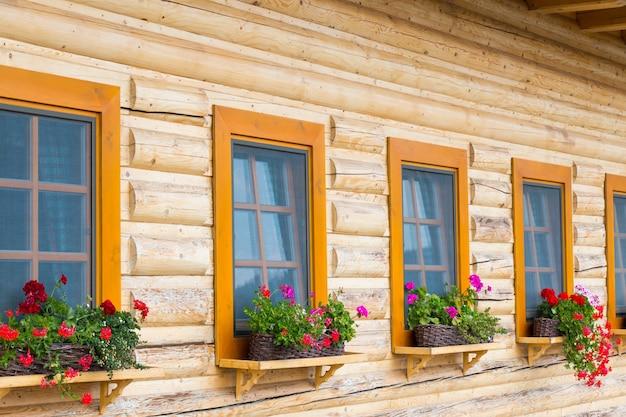 スロバキアのコテージの木製窓辺にある植木鉢の色とりどりの花