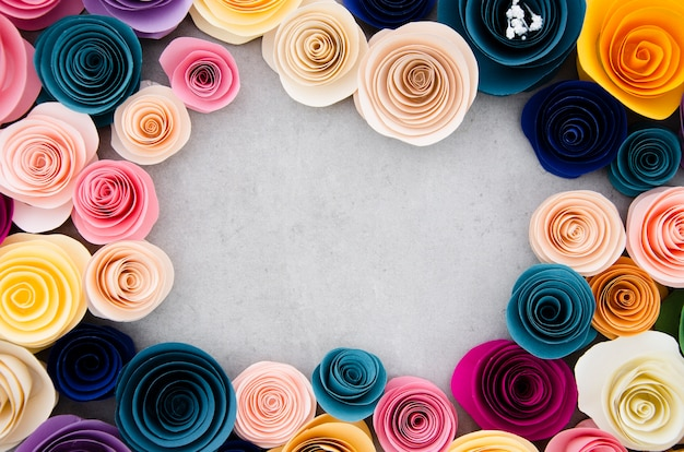 Colourful frame with paper flowers on cement background