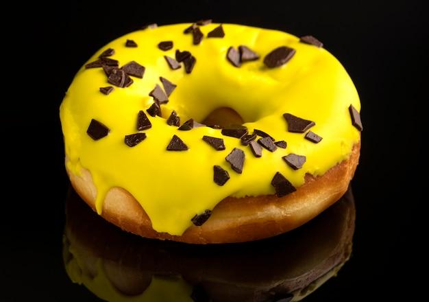 黒の背景にカラフルな艶をかけられたドーナツ黄色のクリームとダークチョコレートの部分で飾られたトッピングの1つのドーナツ