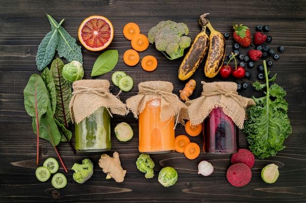 Красочные здоровые смузи и соки в бутылках с свежих тропических фруктов и суперпродуктов на деревянных фоне.