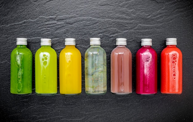 Colourful healthy smoothies and juices in bottles on dark stone background with copy space.