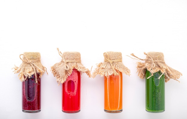 Colourful healthy smoothies and juices in bottles on white background with copy space.