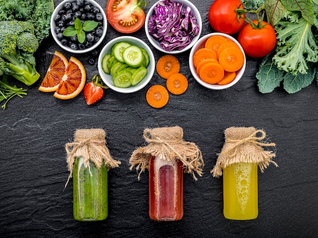 Colourful healthy smoothies and juices in bottles with fresh tropical fruit on dark stone background.