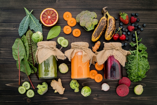 Colourful healthy smoothies and juices in bottles with fresh tropical fruit and superfoods on wooden background.