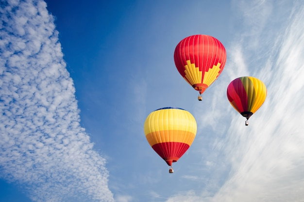 Colourful hot air balloons flying over white clouds and blue sky.