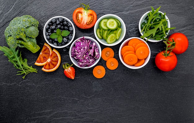 Colourful ingredients for healthy smoothies and juices on dark stone background with copy space.