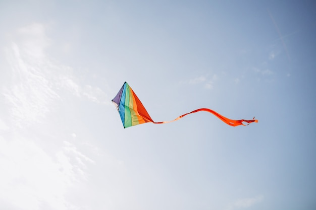 A colourful kite flying against a blue sky.