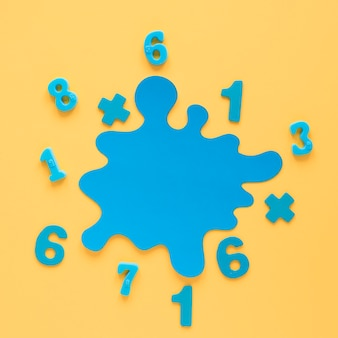 Colourful math numbers and blue stain top view