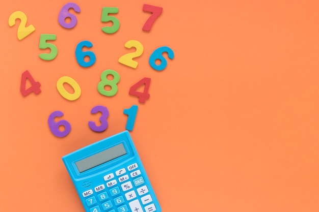 Numeri matematici colorati con calcolatrice su sfondo spazio copia