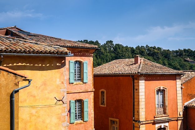 カラフルな古い家の窓シャッター中世の黄土色の村ルシロンの色とりどりの瓦屋根