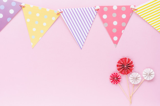 Colourful paper flag with red and white paper fan on pink background for party decoration