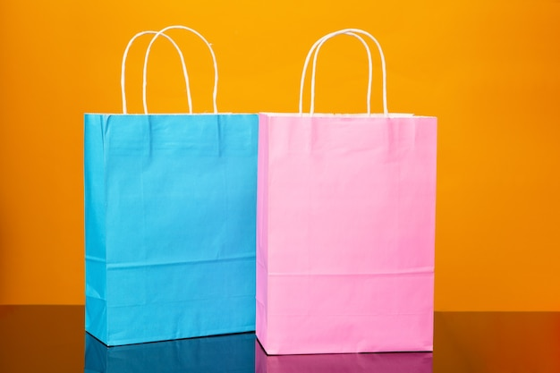 Colourful paper shopping bags on black glass table and yellow