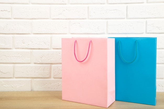 Colourful paper shopping bags on light wall