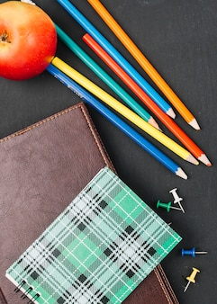 Colourful pencils among notebooks