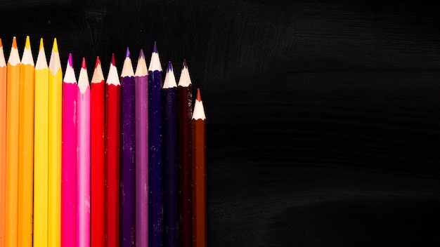 Colourful pencils on black background