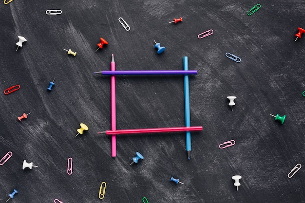 暗い背景上の正方形の形でカラフルな鉛筆