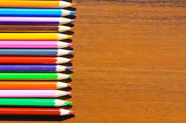 木製の背景にカラフルな鉛筆