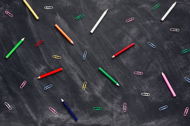 Colourful pencils and paper clips on blackboard