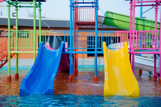 Colourful plastic slides in water park in the sunlight
